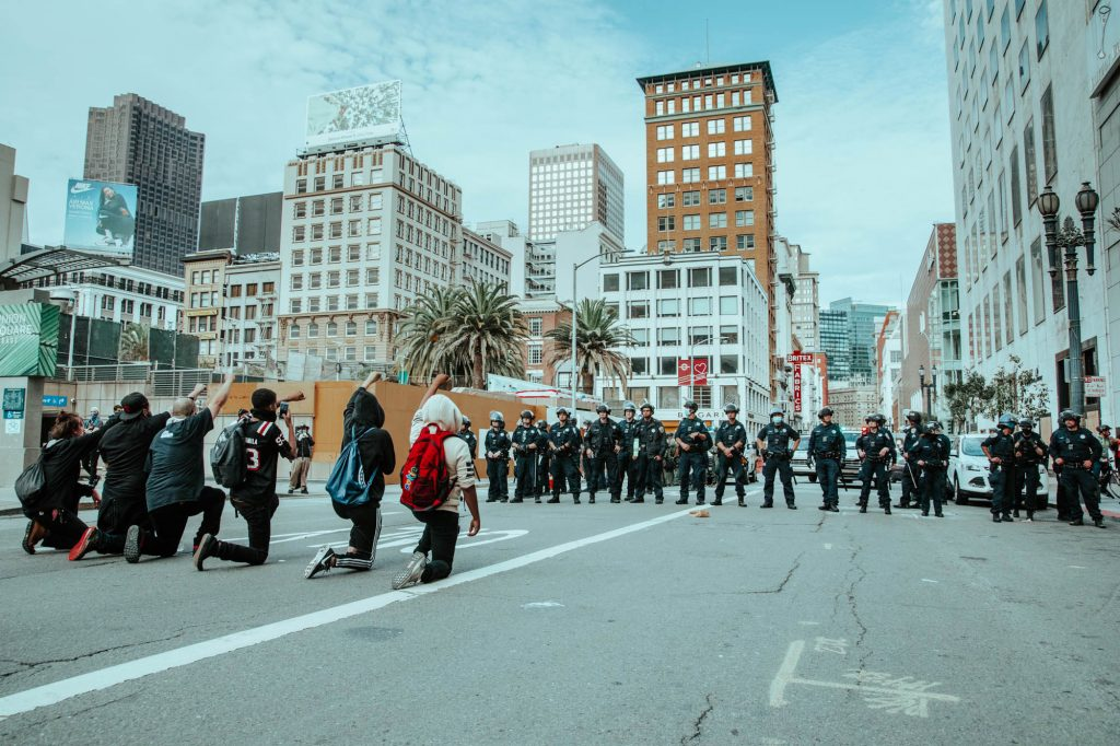 In the background, police stand in a line, blocking off Geary Street. In the foreground, several protestors make a line facing them, kneeling down with their fists in the air.