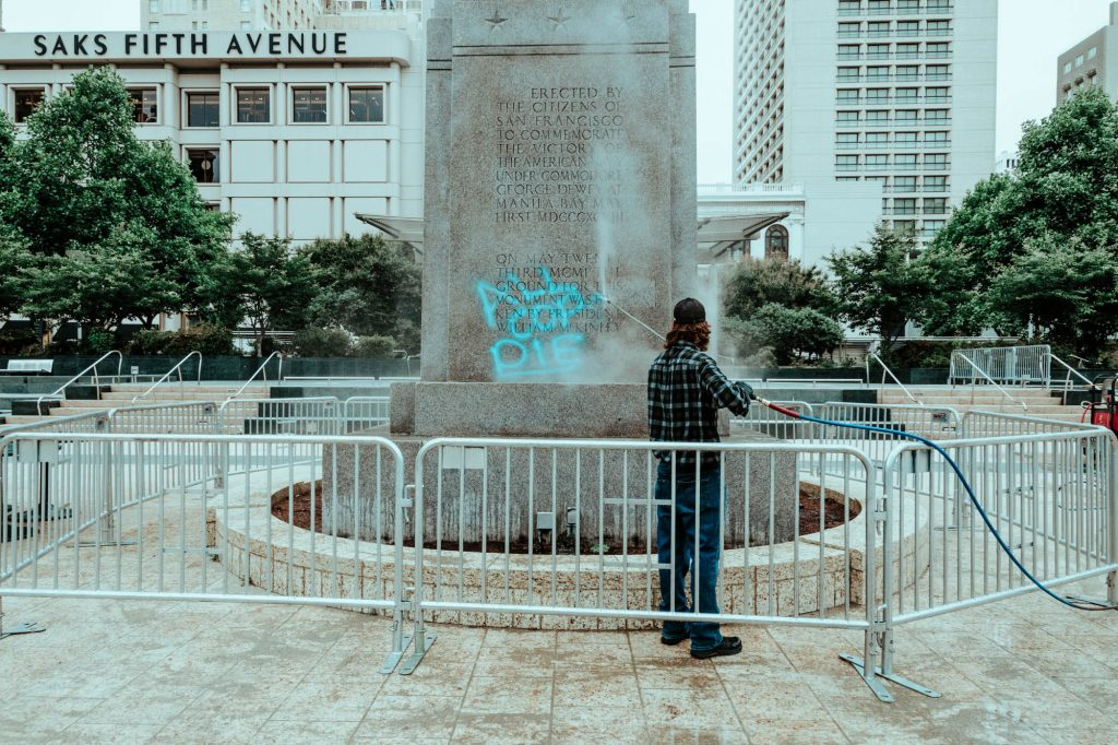 "A man with a power washer removes anti-police graffiti from Union Square's Dewey Monument. The graffiti says ""all cops die"" in blue spray paint."