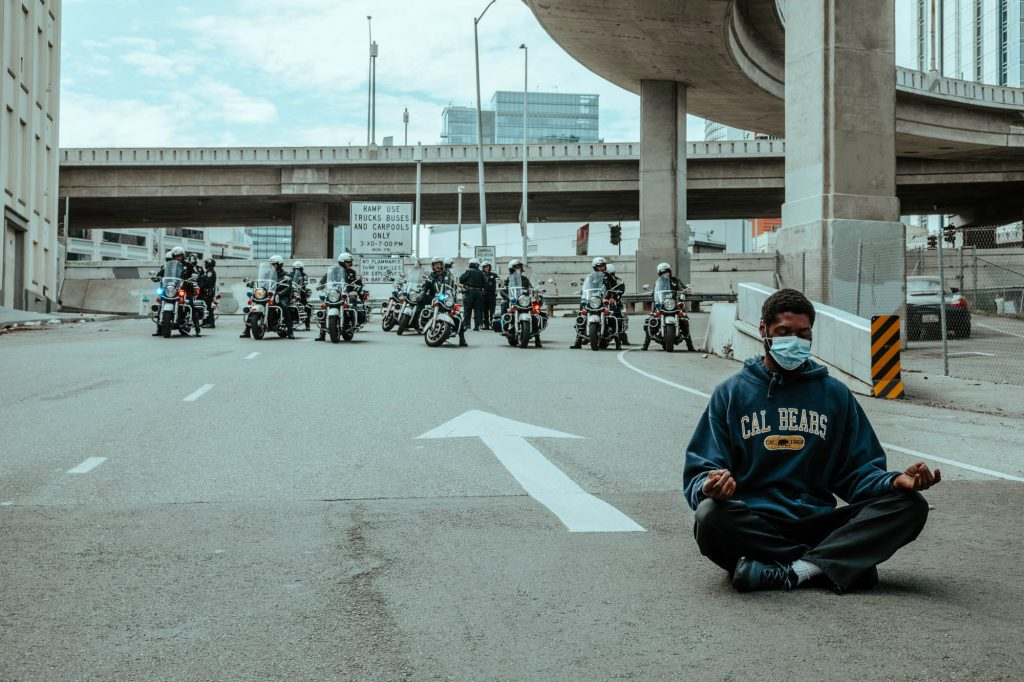 In the foreground, a protester sits on the onramp to the Bay Bridge. He is cross legged in with his hands on his knees and his eyes closed. Behind him, a line of police of motorcycles keep protesters from marching onto the Bay Bridge.