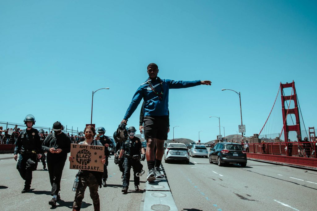 A protestor walks on the median of the Golden Gate Bridge with a megaphone.