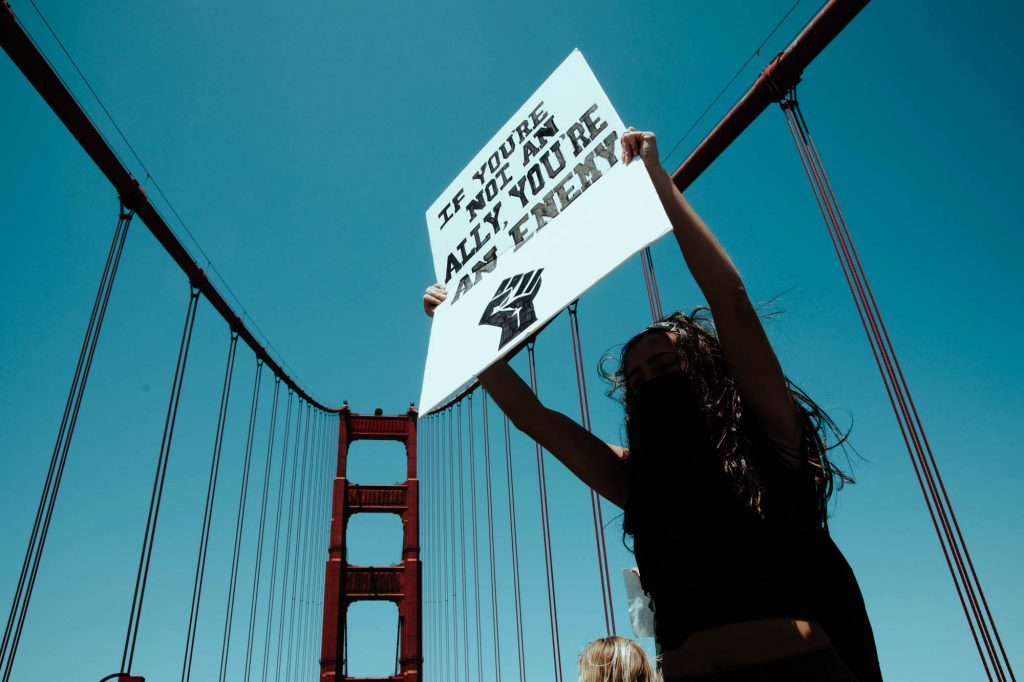 "A protester holds a sign that says ""if you are not an ally you're an enemy"" with the black power fist below it. Behind her, the blue sky and a one of the classic bridge towers can be seen."