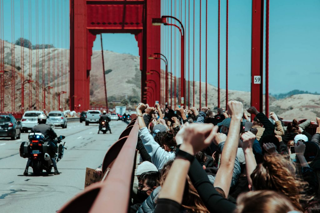 Protesters kneel together and raise their fists on the Golden Gate Bridge.