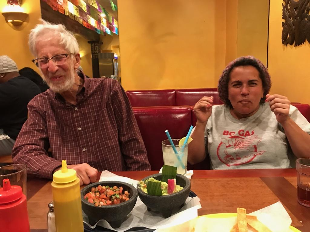 Osha and Andrea laugh as they eat Mexican food together at a restaurant.