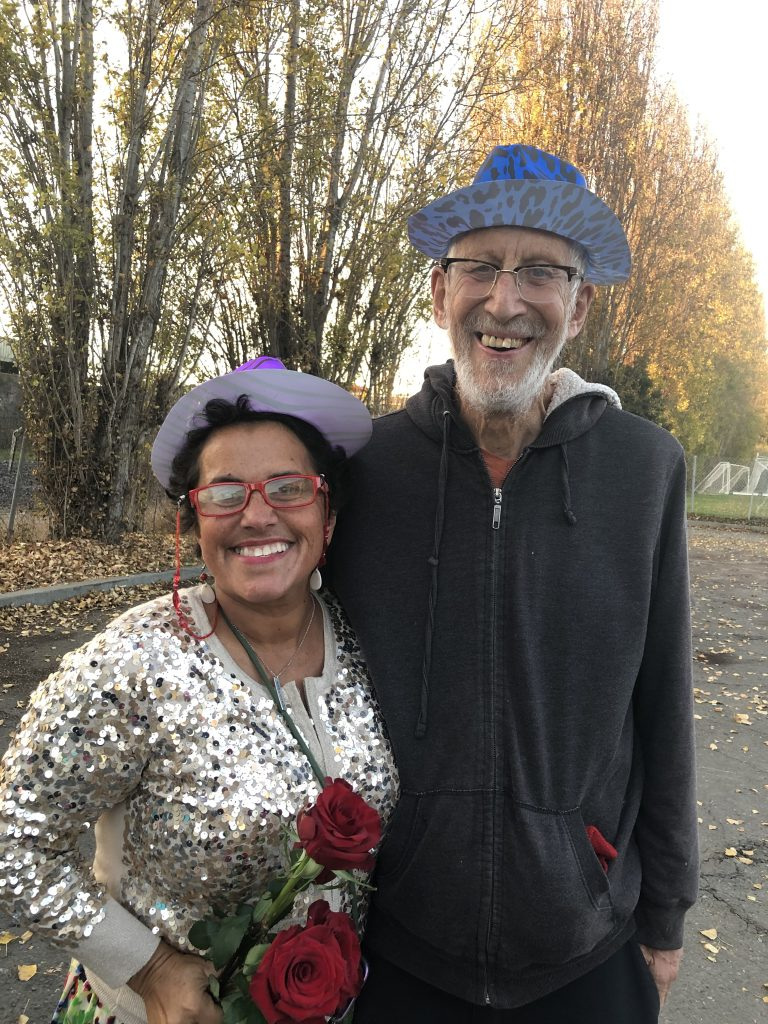 Osha and Andrea are dresses up wearing hats and carrying flowers. They are dressed up for the wedding of encampment residents Sarah and Kevin.