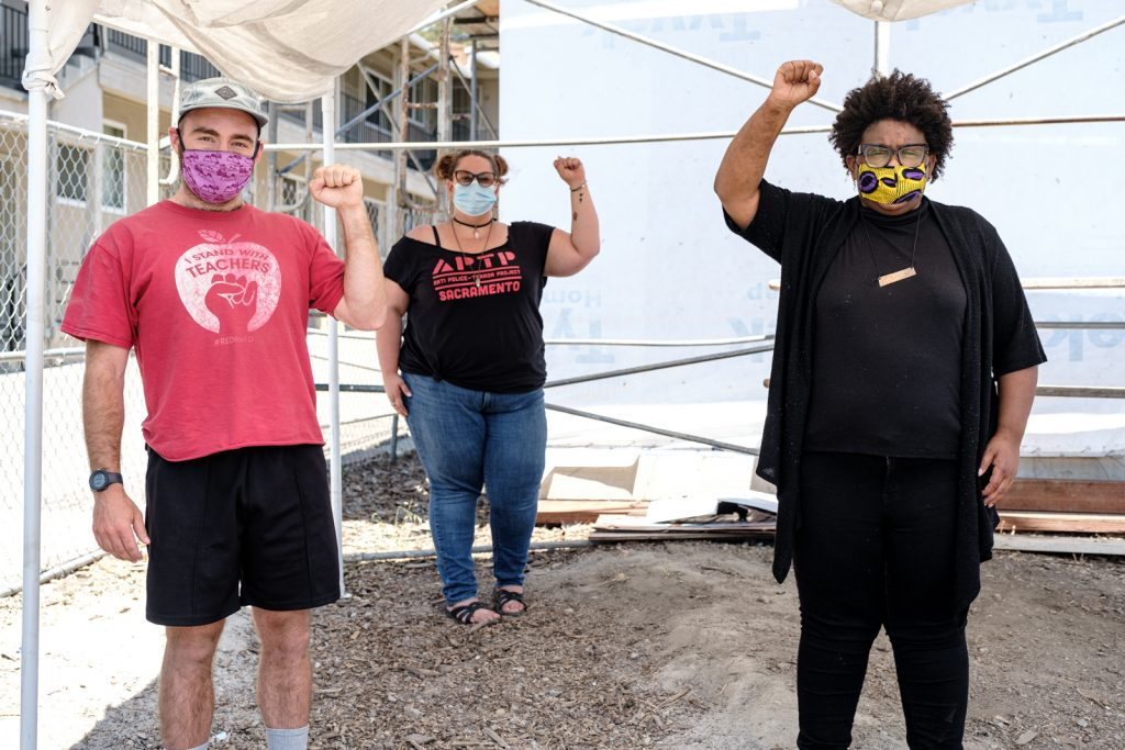 Three MH First volunteers pose for a photo wearing masks and holding up the fist of black power.