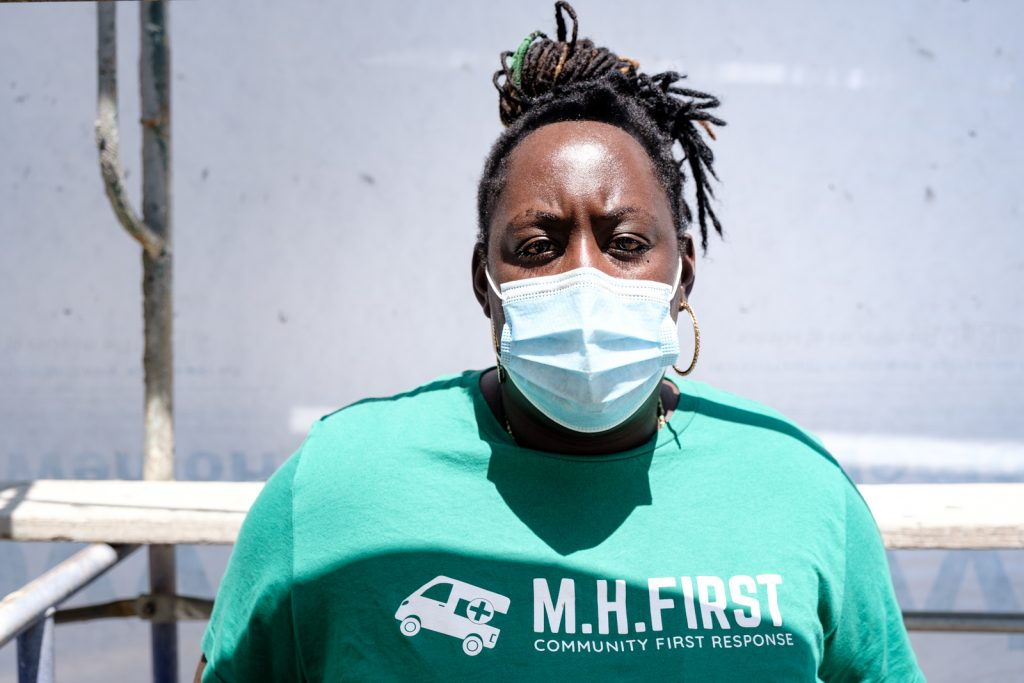 "Mental Health First Program Coordinator Asantewaa Boikin wears a mask and a green shirt that says ""MH First, community first response)"