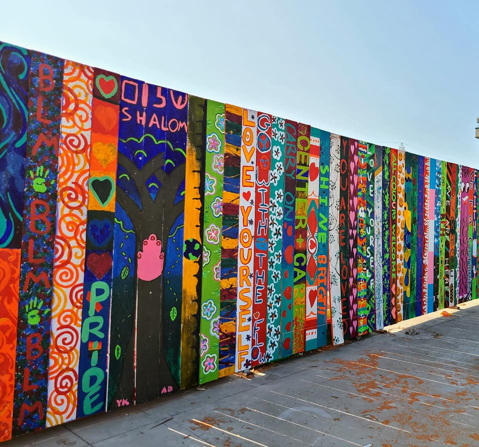 A photo of a wooden fence, Each plank of the fence has been painted by a different artist. They are colorful and contain images and writing.