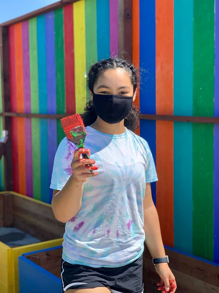 A young painter stands in front of a rainbow fence with a paintbrush in her hand.