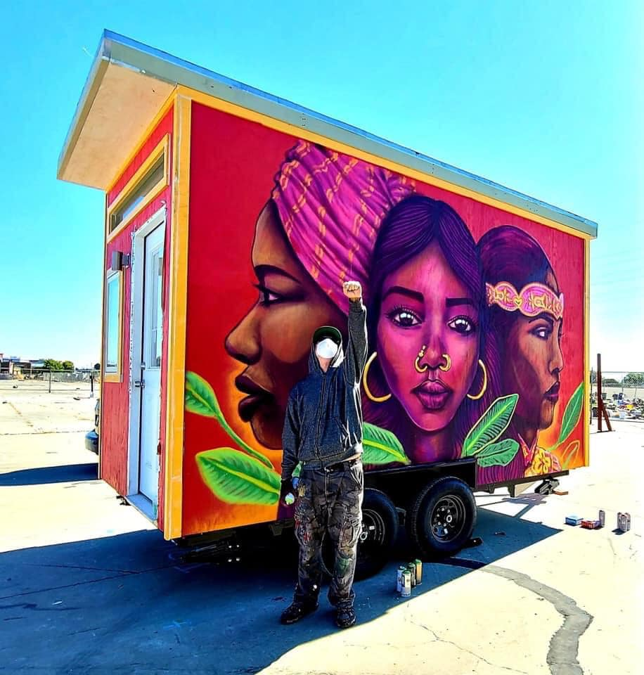 An artist stands in front of a beautiful mural on a tiny home with his fist up in the air in celebration. The mural is pink and red, of three women.