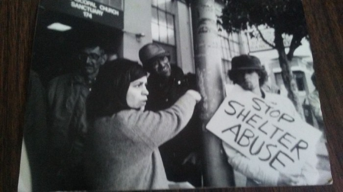 Black and white photograph of a Homeless Union Protest in San Francisco sometime in the late 80s. Sarah Menefee is front center left. Mike Lee is not in the photo.