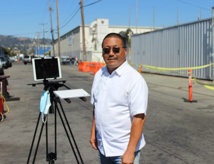 "Derrick Soo, friend of Mike Lee, standing in front of an ipad propped up on a tripod, which he uses to do his broadcast ""The Journey Home"" about his experiences with homelessness."