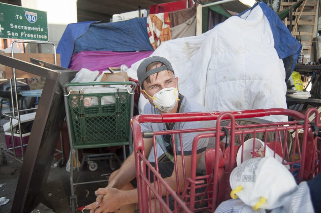 A man sits in the midst of a homeless encampment, with shopping carts and tents in front of him and behind him. He is wearing an N-95 mask to protect against the smoke.