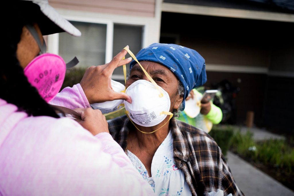 A volunteer gently puts a mask on an older woman's face.