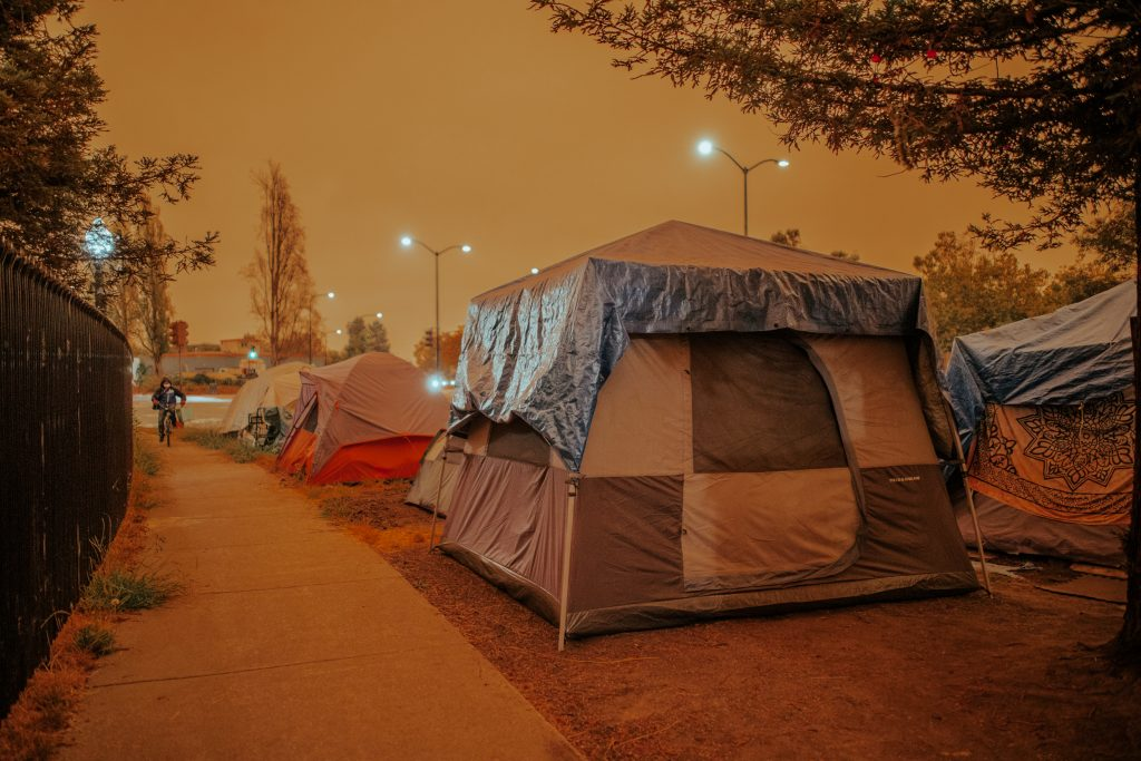 An eerie glow engulfs South Berkeley's Here/There encampment on Wednesday as wildfires rage in California.