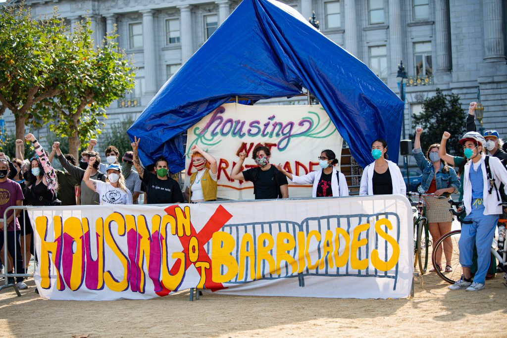 """Protestors stand inside the structure they built outside of San Francisco's City Hall. The structure is made out of  metal barricades and blue tarps. In front is a colorful sign that reads """"housing not barricades."""""""