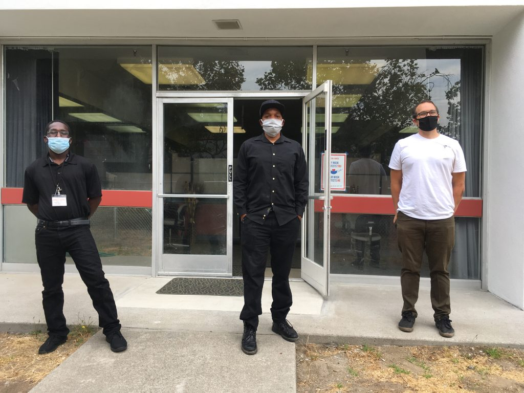 Jermane Gray, Joey Harrison, and Jeremy Pfiefer stand in front of Village of Love, all wearing face masks.