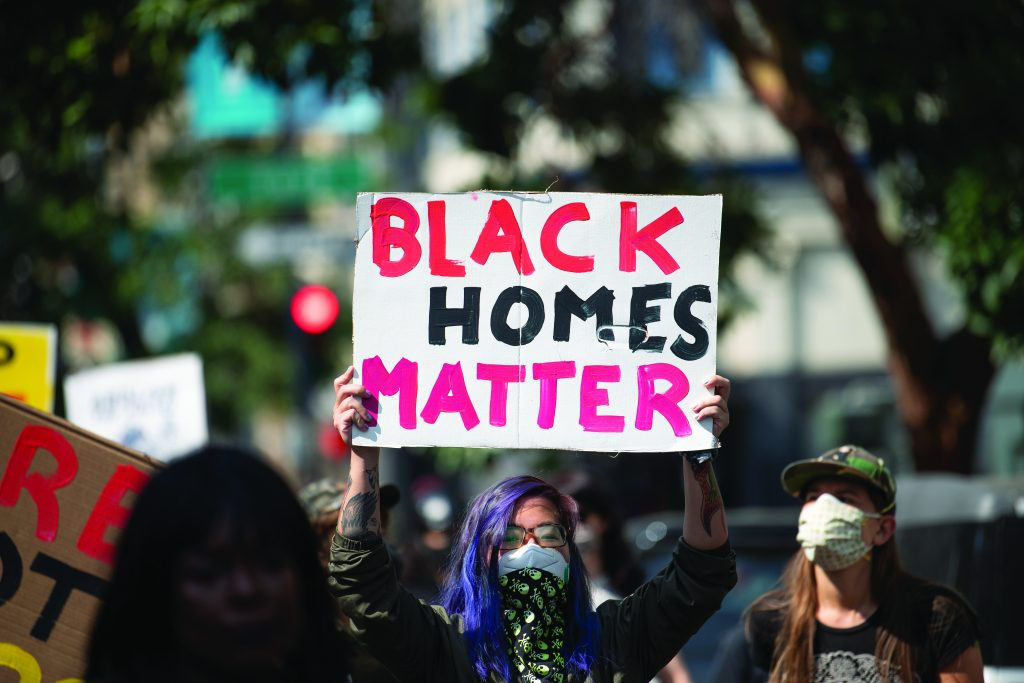 """A protestor holds a sign that reads """"Black Homes Matter."""""""