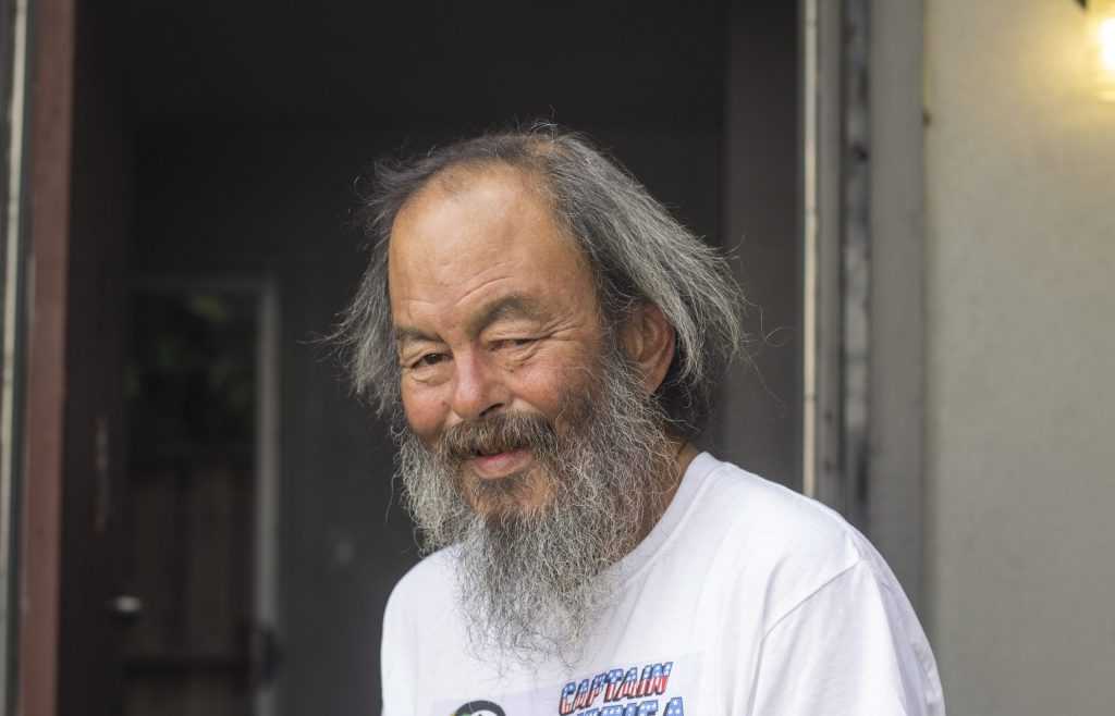 Mike Lee smiles for a photo after obtaining housing in 2017. He has a long grey beard and is wearing a white shirt.