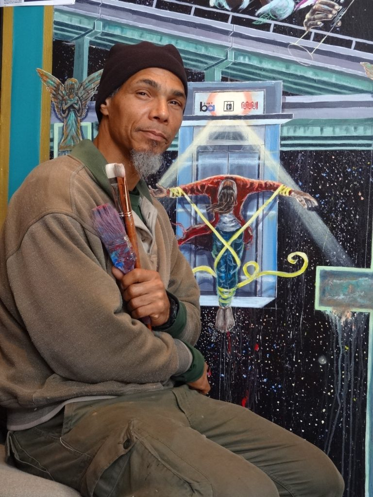 Ronnie Goodman sits in front of a painting he is working on with a paint brush in his hand.