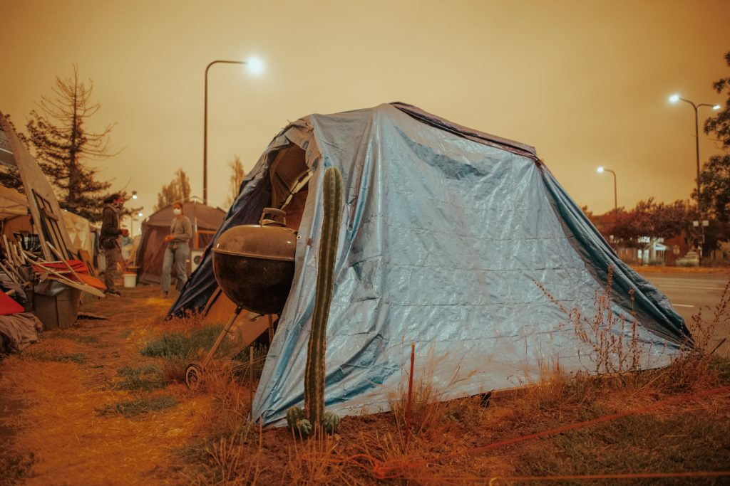A tent acts as shelter under the orange sky in South Berkeley. A cactus grows out of the ground next to the tent, which has a blue tarp draped over it.