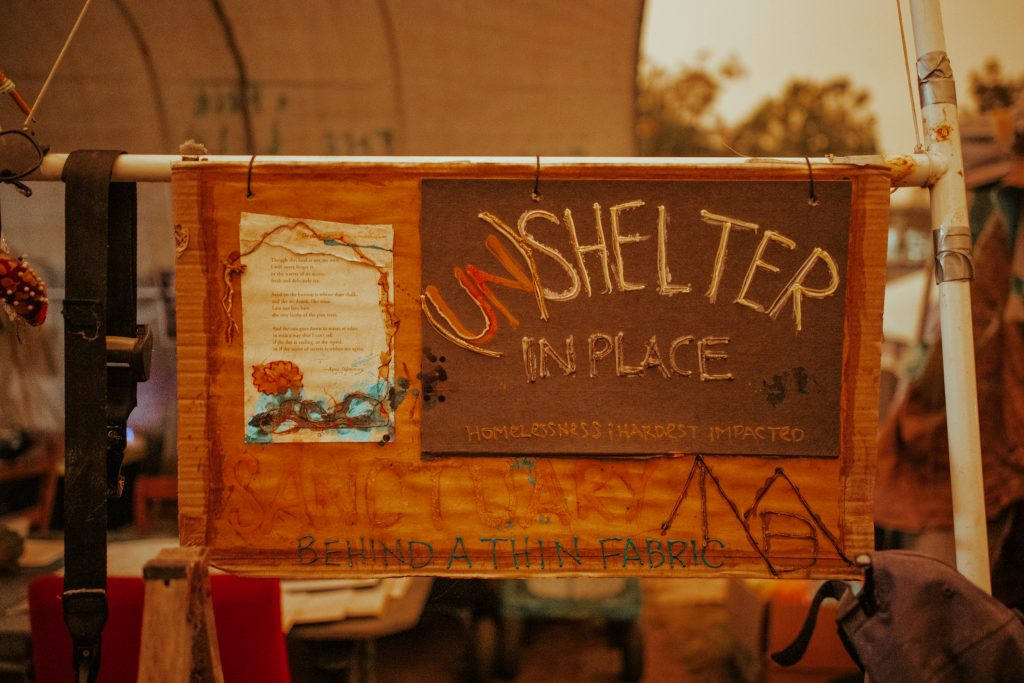 "A piece of artwork reads ""(Un)Shelter In Place"""