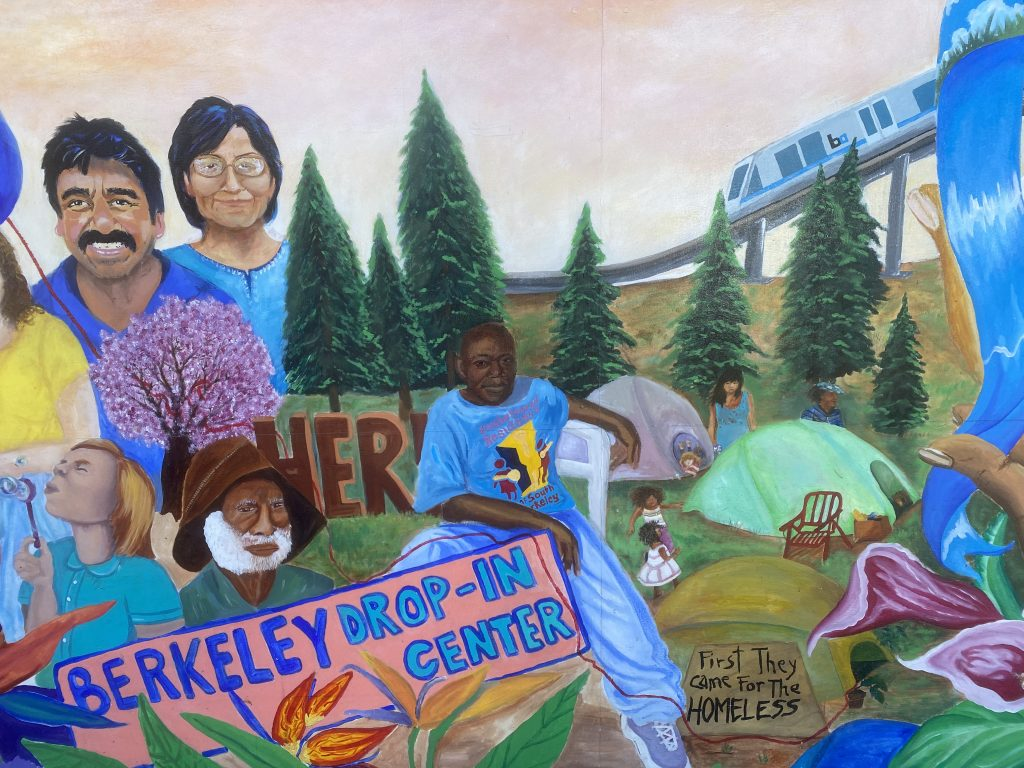 A colorful mural containing several South Berkeley staples including several individuals, some tents, the Here/Tehre encampment, a BART train, and Alando Williams sitting front and center.