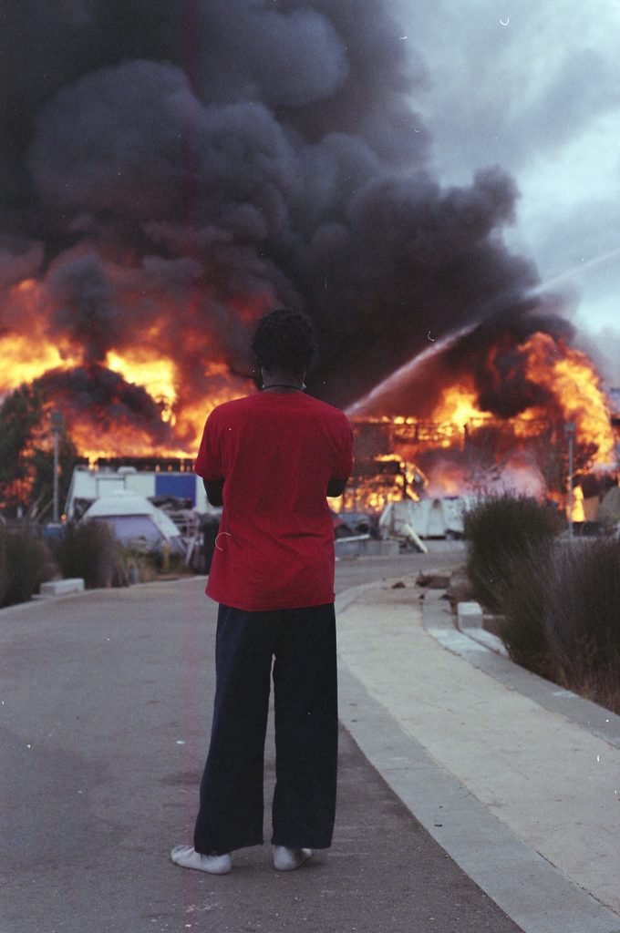 A woman with her back facing the camera watches a building engulfed in flame burn before her. She is wearing a red t-shirt, black pants, and socks. Her arms are crossed as she observes the building go up in dramatic red and orange flames.