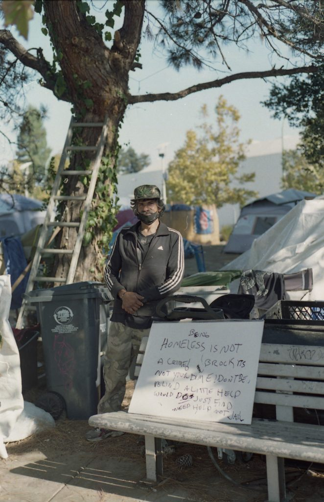"An encampment residents stands next to a tree. In front of him, a sign he made reads, ""Being homeless is not a crime!"" Behind him, tents are visible."