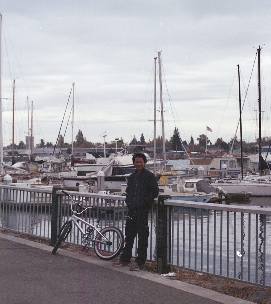 An encampment resident leans against a railing with his bike. Behind him the water of the Marina and sail boats are visible.