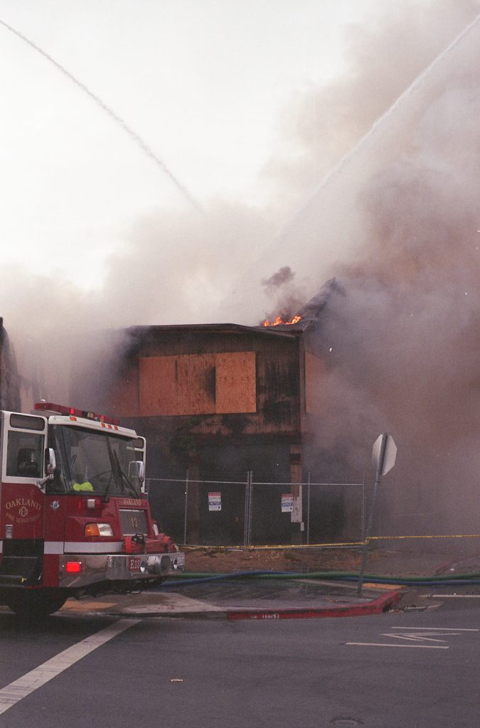 The Cryer Building is engulfed in pinkish smoke. On the left, the front of a fire engine can be seen.