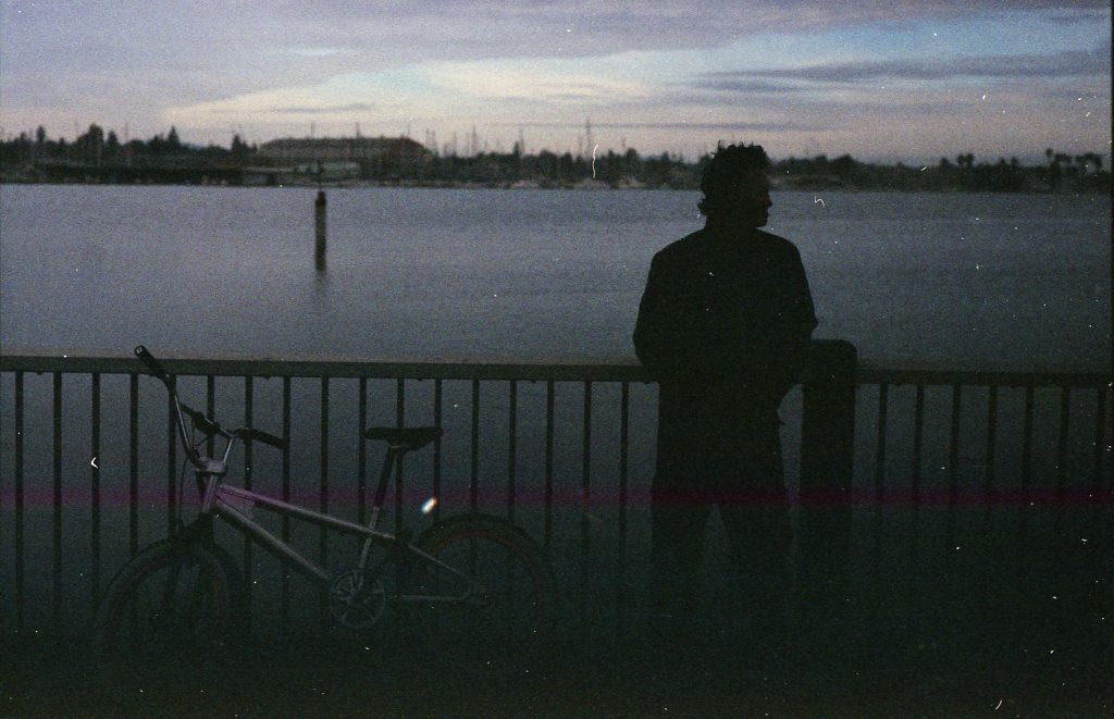 The silhouette of an encampment resident and his bike leaning up against a fence. Behind the resident lies the Marina, with water and sailboats visible.