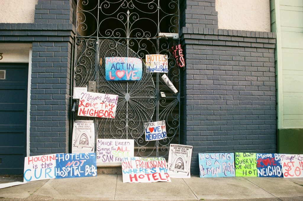 "Protest signs adorn SF Mayor London Breed's doorstep during a protest in April, 2020. They say ""Act in Love,"" ""Hotels not hospital beds, and ""Housing is the cure"", amongst other things."