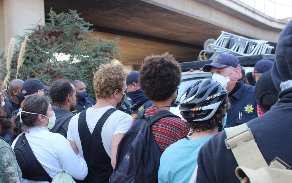 Protestors in helmets face off with an Oakland Police Officer.