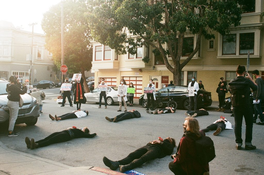 "Protestors lie down in the street wearing all black during a ""die-in"" protest outside SF Mayor London Breed's home."