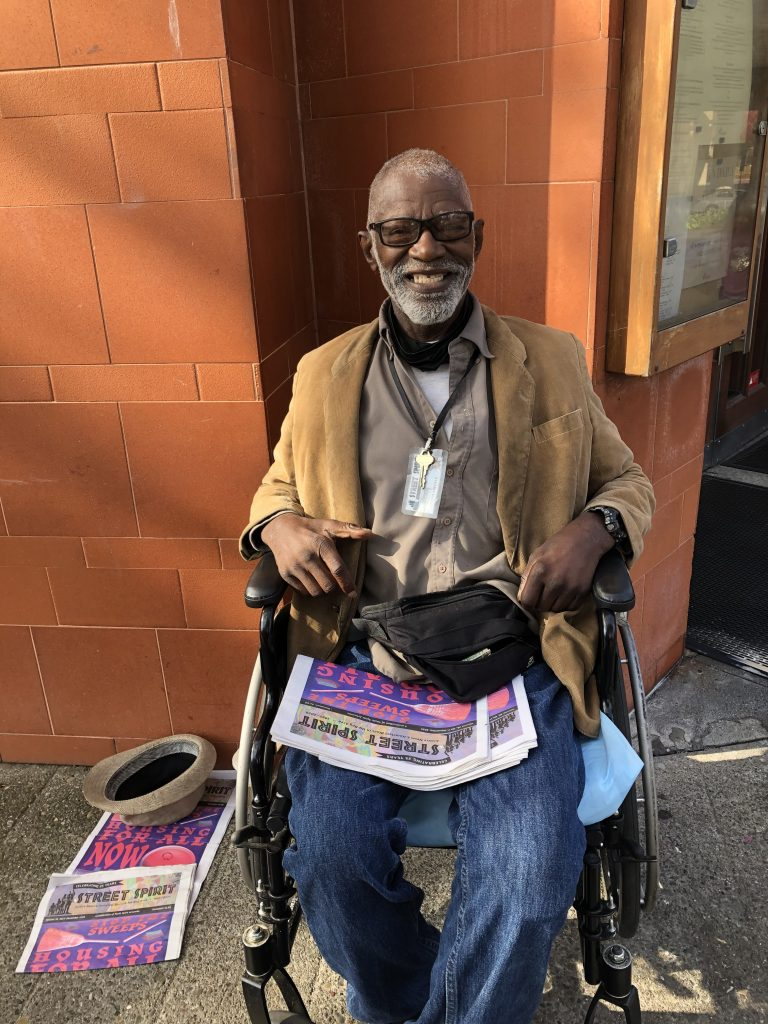 Al mayfield sits outside Oliveto restaurant in the Rockridge neighborhood of Oakland, wearing a wide smile. He sits in his wheelchair wearing a tan blazer. In his lap he has a pile of Street Spirit newspapers.