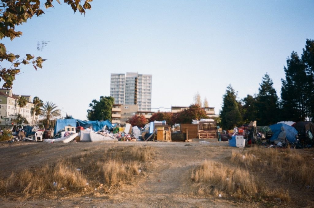 A photo of a homeless encampment surrounded by buildings in Downtown Oakland in the background.