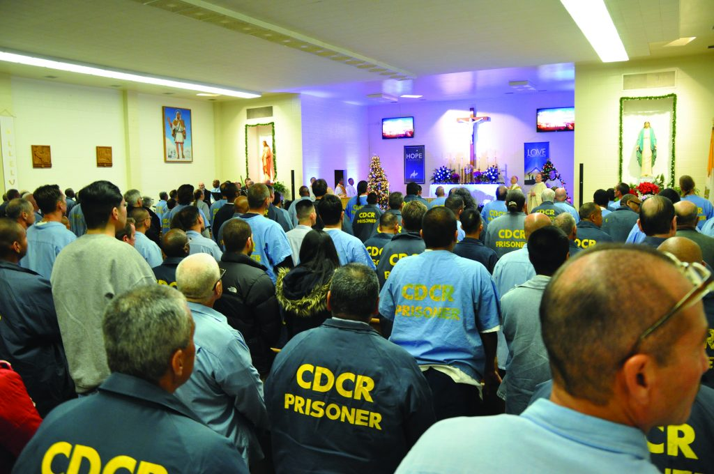 "Christmas inside the chapel at San Quentin. The words ""CDCR Prisoner"" can be seen on the back of the men's shirts."