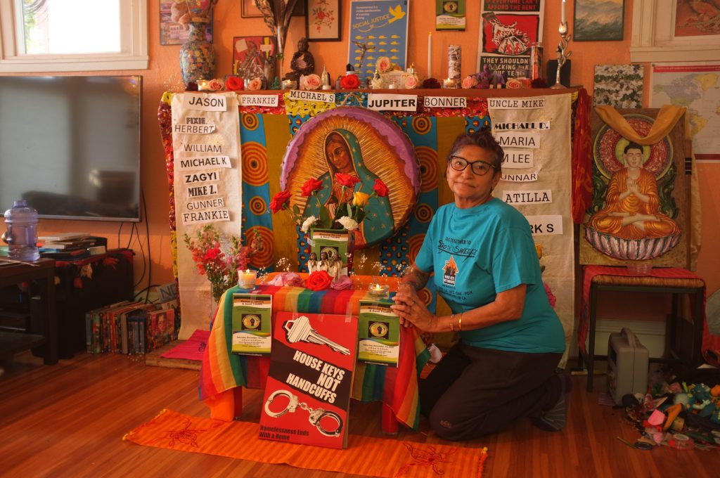 boona cheema sits in her home in front of an altar for lives lost on the street. The altar consists of flowers, photos, and names.