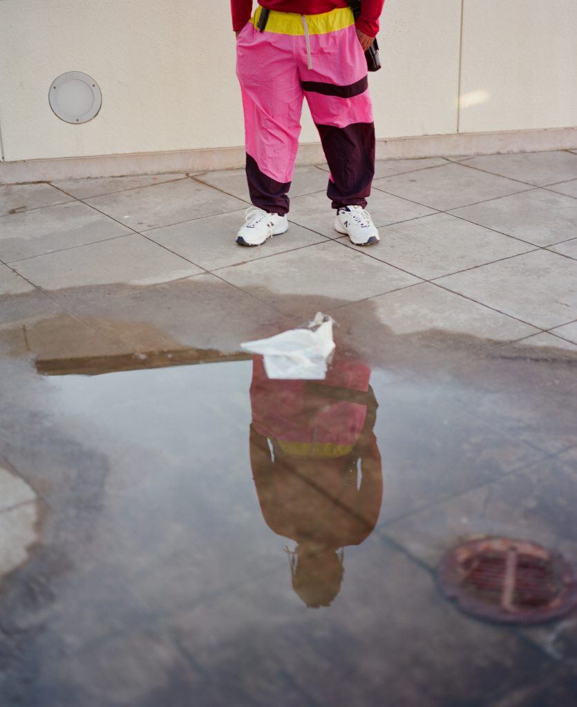 Lil B's reflection in a puddle outside the Cliff House in San Francisco. He is wearing hot pink pants and white sneakers.