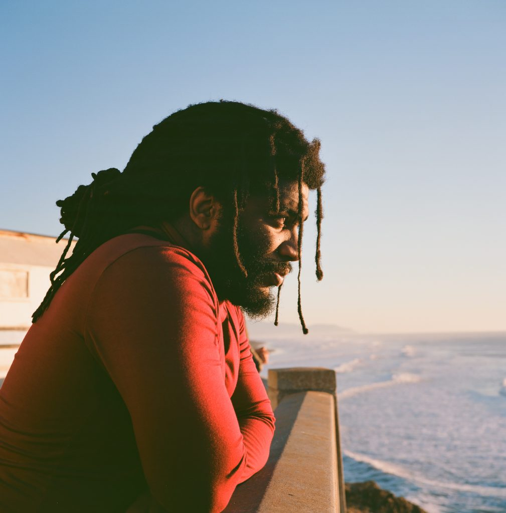 Li B looks out over the ocean. The photo is a profile. You can see his contemplative stare as he looks out over the ocean. Dreadlocks hang in front of his face. His red T-shirt poses a bright contrast against the blue ocean in the background.