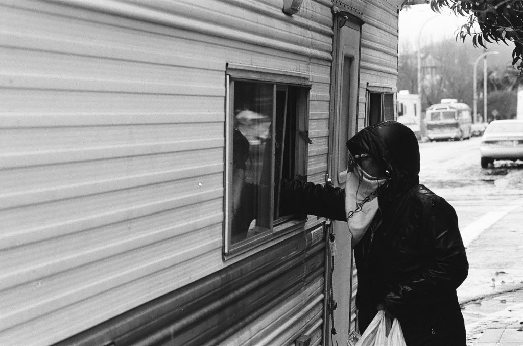 Yesica Prado hands supplies to a person through the window of their RV. It is raining and Prado's hair is wet. She is wearing a raincoat.