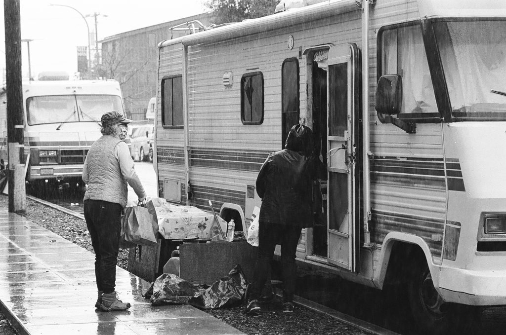 Prado and another volunteer hand supplies into the door of an RV. The road around them is wet.