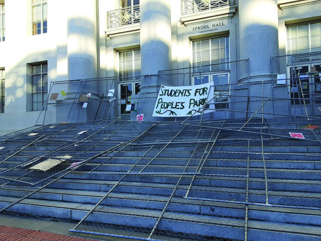 "Pieces of fencing piled on the steps outside of Sproul Hall. A sign that reads ""Students for People's Park"" hangs on the fencing."