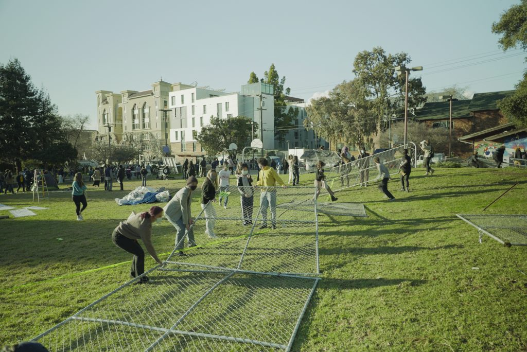 A group of 10 or more students gran hold of a piece of fencing which has been torn to the ground. They stand in a green, grassy People's Park.