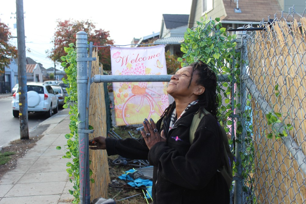 """A Black woman stands in front of a chain link gate that has been decorated by a plastic ivy plant that has been woven through the metal fencing. A sign that reads """"welcome"""" hangs on the gate, which is an entrance to the 37MLK homeless encampment. The woman looks up at the sky and holds one hand to her heart, as if in prayer or thanks to a higher being. She has a smile on her face."""