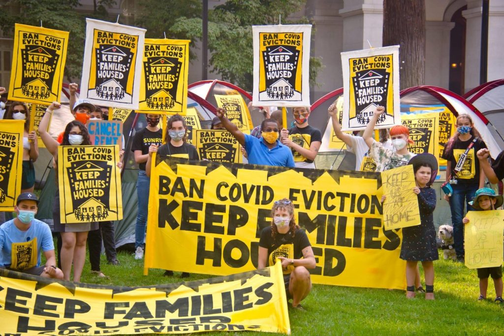 """A group of people holding banners and signs that say """"ban COVID evictions, keep families housed."""" People have masks on and some are holding fists in the air. It is a mixed age group containing both young children and adults."""