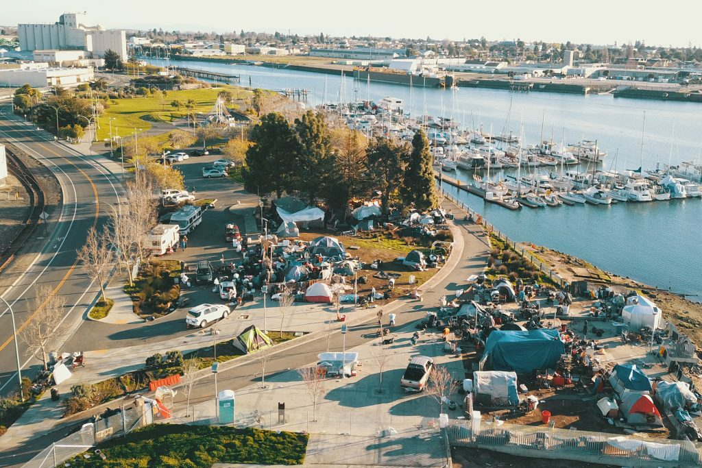 An aerial view of the encampment at Union Point Park. Many tents and structures can be seen in the park, which butts up right against the marina, where many boats are parked.