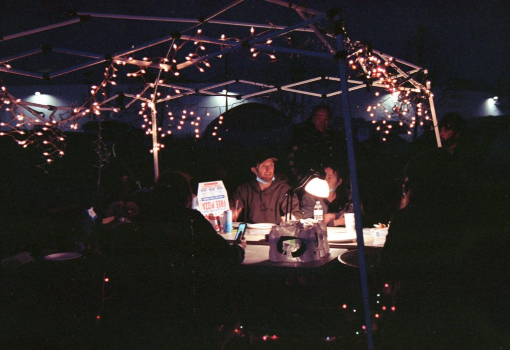 In the dark, a group of encampment residents and their supporters sit under a tent and strategize. Their faces are lit up by a string of twinkle lights hanging from the easy-up above them.