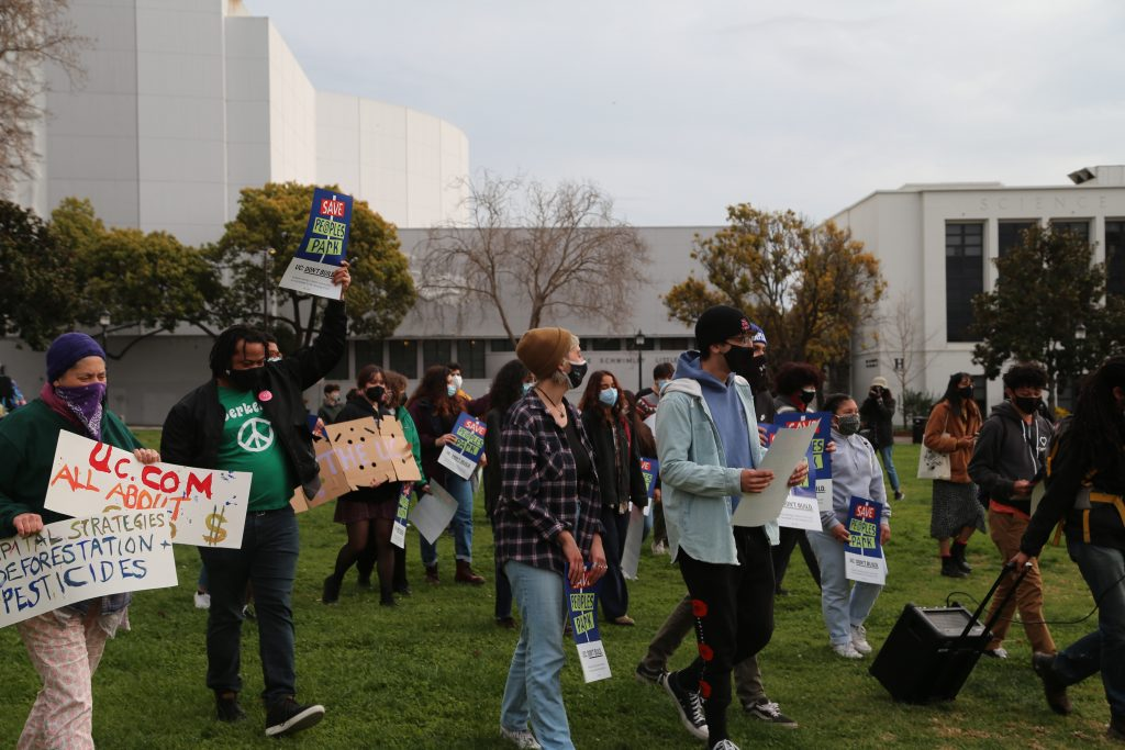 "Students march through MLK Civic Center park holding protest signs that say things like ""capital strategies deforestation pesticides"""