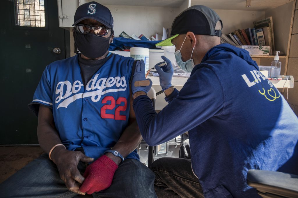 An RN gives the vaccine to a Black man wearing a hat, sunglasses, a Dodgers jersey, and one red glove.